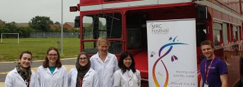 Volunteers for our schools roadshow wear lab coats and stand by a double decker bus