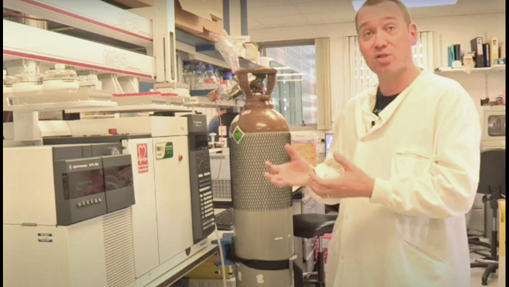 Dr Sam Virtue stands in the lab next to a large mass spectrometer machine