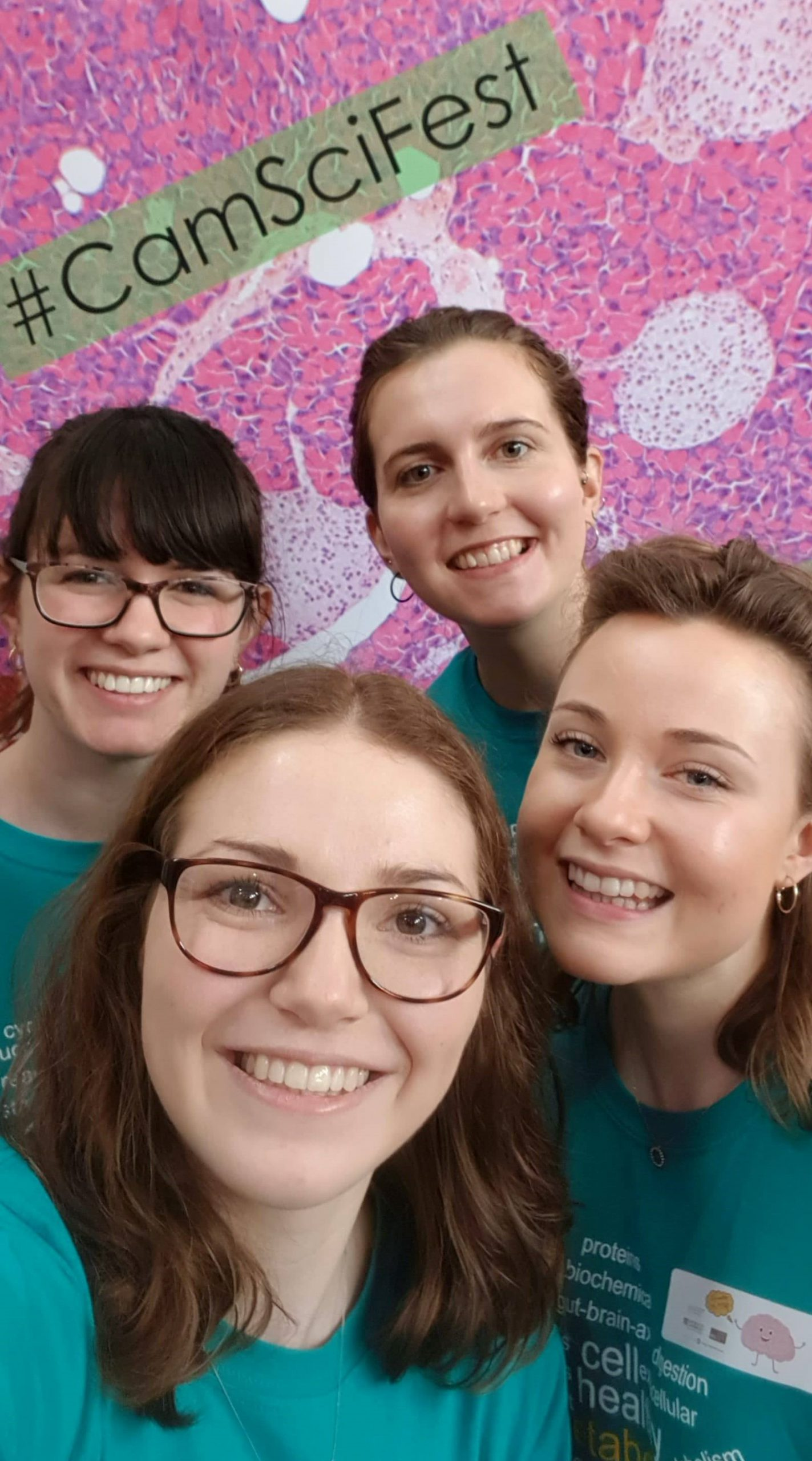 Four Cambridge Science Festival Volunteers pose in front of a colourful selfie wall