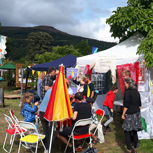 Activity tents and festival-goers with a mountain as a backdrop