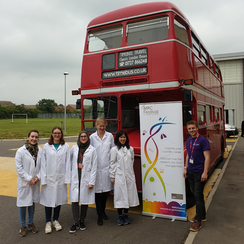Volunteers in lab coats standing by our school roadshow double decker bus
