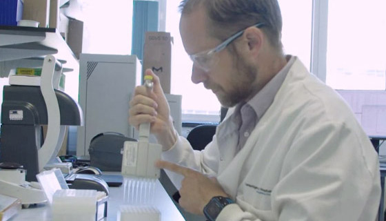 Dr Richard Kay sits in the lab using a multi-channel pipette